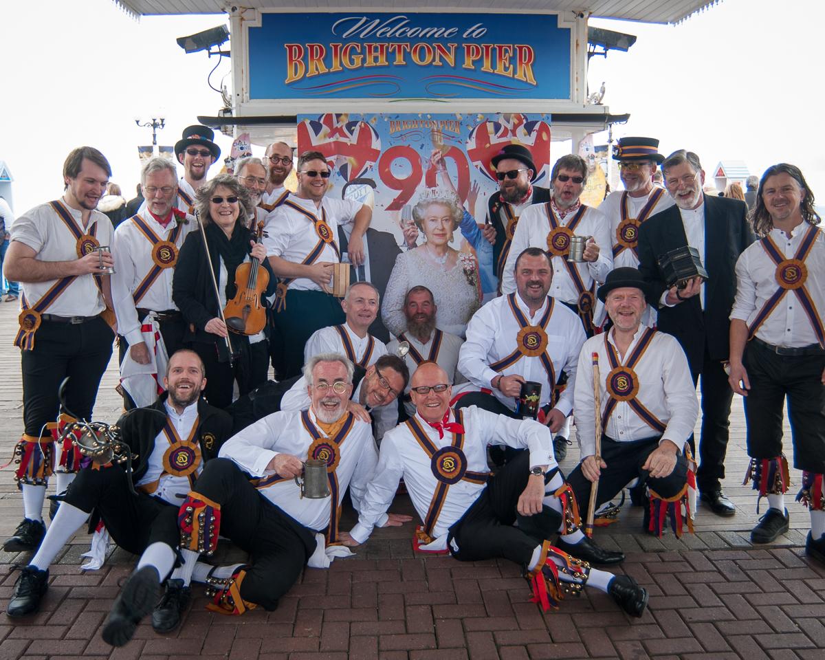 Brighton Morris Men pose in front of the Queen on Brighton Pier