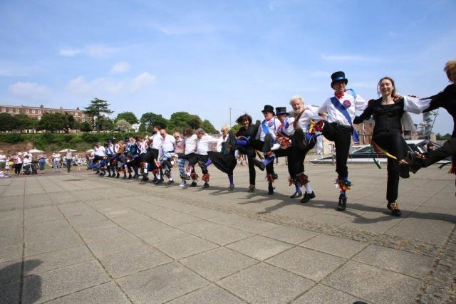 Group of morris dancers in a line, dancing